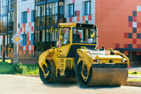 The image Road roller working at road construction site in the city Stock Photo