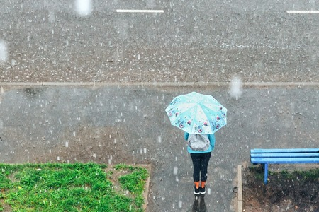 the image girl with umbrella standing under the rain at the bus stop