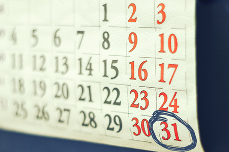 Calendar with dates of month is hanging on the wall, blur except weekends