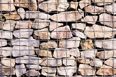 intermittent: Stone wall behind bars