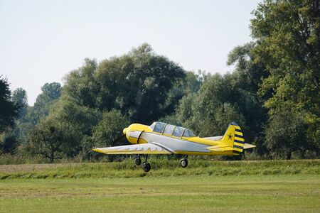 Start of a single-engine yellow-white old sports aircraft Stock Photo