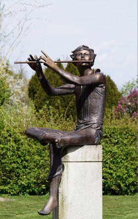 Bronze sculpture of a flute player in the garden