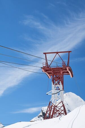Pylon and ropes of the glacier railway between the towering mountains
