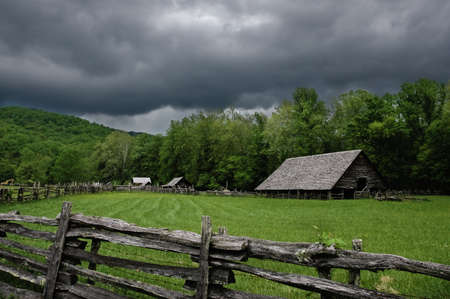 A historic log cabin on a stormy day.
