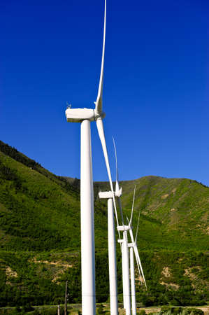 A row of wind turbines against a bright blue sky Stock Photo - 11977502