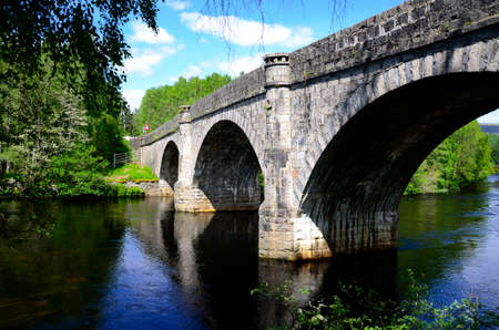 flowing river: An ancient bridge in Scotland over a slow flowing river.