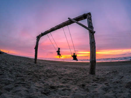 fluctuate: Swinging children on the beach at sunset