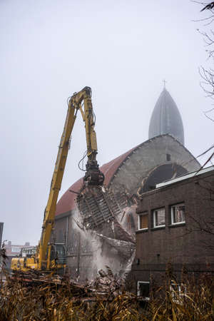 Demolition of church with falling rubble and dust Stock Photo