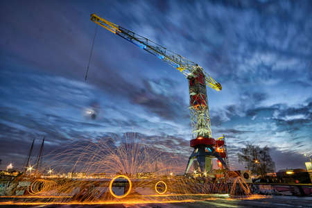 Steelwool spinning in industrial location with crane Editorial