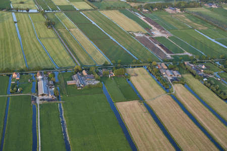 Aerial of modern farms with solar panels on the roof in a dutch meadow landscape