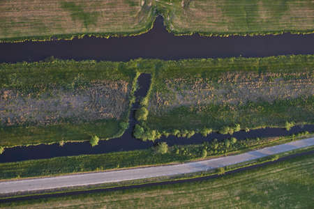 Aerial view of road leading through peat excavation meadow landscape in the netherlands Reklamní fotografie