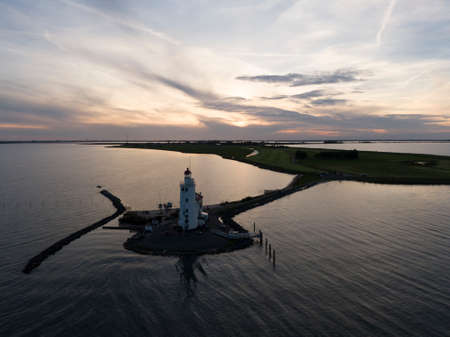 Aerial of lighthouse on peninsula in the Netherlands at sunset