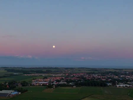 Aerial image of purple sky after sunset with full moon over flat meadow land, sea and village on dutch island Texel