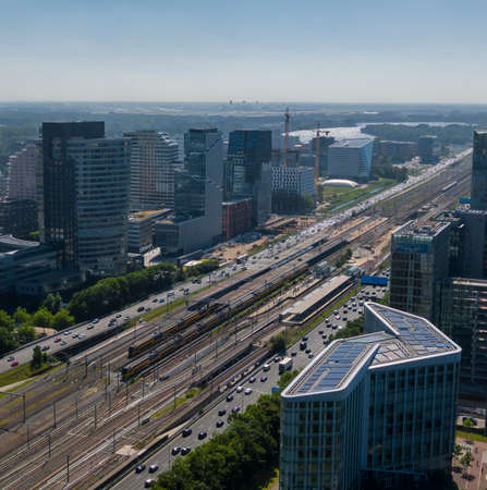 Aerial of the Amsterdam Zuidas business district, showing modern sustainable office buildings and their connection by highway and public transport to Schiphol airport