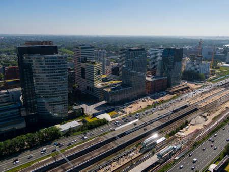 Luchtfoto van moderne kantoorgebouwen op de Amsterdamse Zuidas, verbonden door snelweg en treinstation Stockfoto