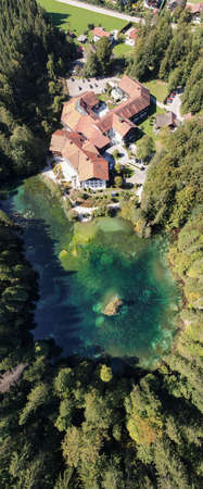 Top down aerial portrait panorama image of hotel resort on beautiful clear blue lake surrounded by trees