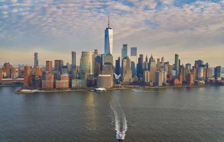 Aerial view of lower Manhattan financial district with modern architecture office buildings shot from helicopter at golden hour