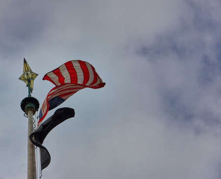 American flag on pole waving in the wind with clouded sky in the background 版權商用圖片