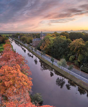 Aerial of the Nyenrode castle next to the Vecht river during an amazing autumn sunset with pink sky and orange colored trees