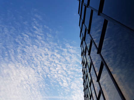 Looking up vertically to the blue sky with light white clouds and modern glass building with black steel elements windows