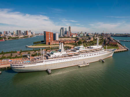 aerial of SS Rotterdam ship moared on Katendrecht land head with skyline of towers and Erasmus bridge in the background