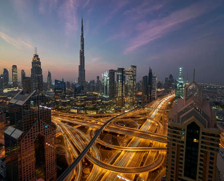 View on highway node and downtown Dubai with tall modernistic skyscrapers during spectacular blue hour with pink and orange clouds
