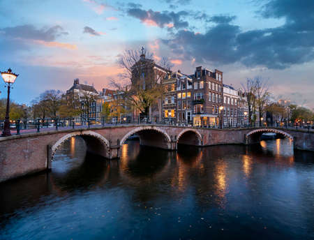 Famous Amsterdam canals with historic houses and stone bridge just after sunset with colorful sky and bluehour lights 版權商用圖片
