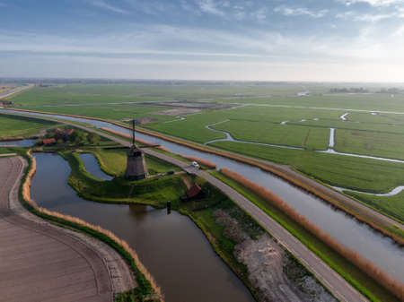Aerial view of Dutch agricultural spring scene with classic windmill, agricultural field and water 版權商用圖片