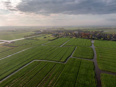 Aerial view of dutch green meadow land with water canals and small village 版權商用圖片