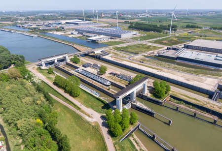 Aerial view of the Princess Beatrix sluice complex in the Netherlands with sustainable energy generating wind mills and solar panels in the background. Waterways transportation infrastructure