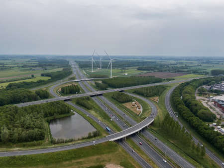 Aerial view of highway junction and traffic node with curved overpass roads through green landscape with energy generating wind turbines in the Netherlands