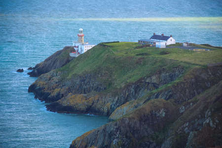 helipad: Lighthouse on a cliff in the sea with a helipad.
