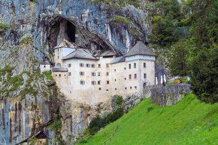 reigns: Predjama Slovenia September 6 2014. The Predjama Castle reigns over the surrounding area perched high up in a vertical cliff.