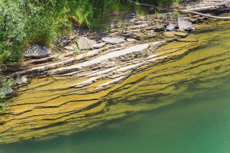 rock layers: Bank of emerald mountain river consisting of layers of rock.