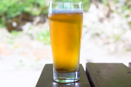 unbottled: Glass of light beer closeup on a wooden table. Stock Photo