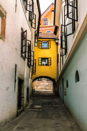open windows: Narrow european street, open shutters in windows and yellow house between.