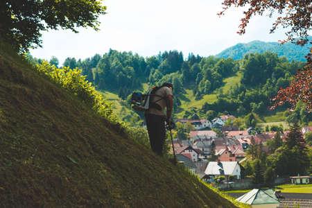 mows: Man mows a green grass on a mountain. Stock Photo