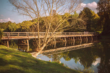 foot bridges: Old wooden bridge is reflected in the clear river.