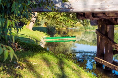 green boat: Green boat parked behind old wooden bridge.