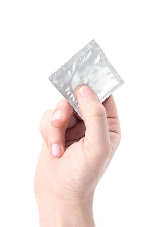 Hand holding a condom on white background photo