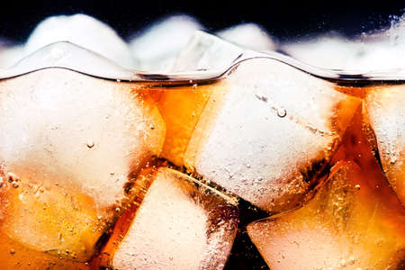 carbonation: Glass of cola with ice cubes close-up