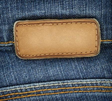 denim: Etiqueta de pantalones de cuero blanco cosido en un pantalones vaqueros. Puede utilizarse como fondo para el texto.