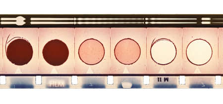 16mm motion film strip sample with frames, soundtrack and six circles. Isolated on white background. photo