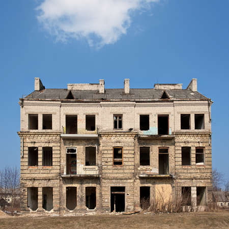 Abandoned damaged old house against blue cloudy sky