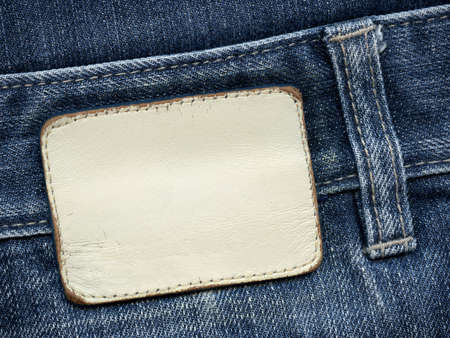 inner wear: Blank leather jeans label sewed on a blue jeans. Can be used as background for your text.