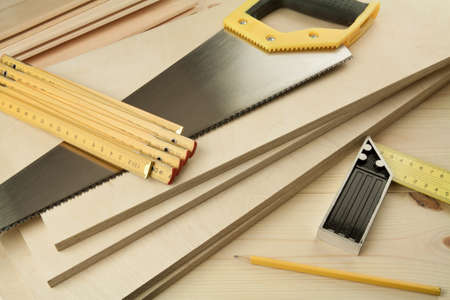craft work: Wood working tools on a wooden boards background. Including saw, ruler, pencil, square.
