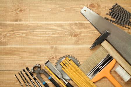 alicates: Herramientas de trabajo sobre un fondo de tablas de madera. Incluyendo Sierra, gobernante, taladro, clavos, alicates, martillo, pincel, hilo, cincel. Foto de archivo