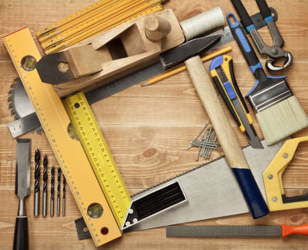 carpenter items: Working tools on a wooden boards background. Including saw, ruler, drill, nails, pliers,hammer, brush,thread,chisel and other.