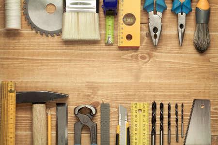 hardware: Herramientas de trabajo sobre un fondo de tablas de madera. Incluyendo Sierra, gobernante, taladro, clavos, alicates, martillo, pincel, hilo, cincel y otros.
