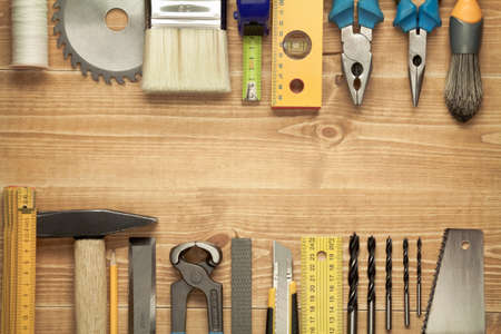 planking: Working tools on a wooden boards background. Including saw, ruler, drill, nails, pliers,hammer, brush,thread,chisel and other.